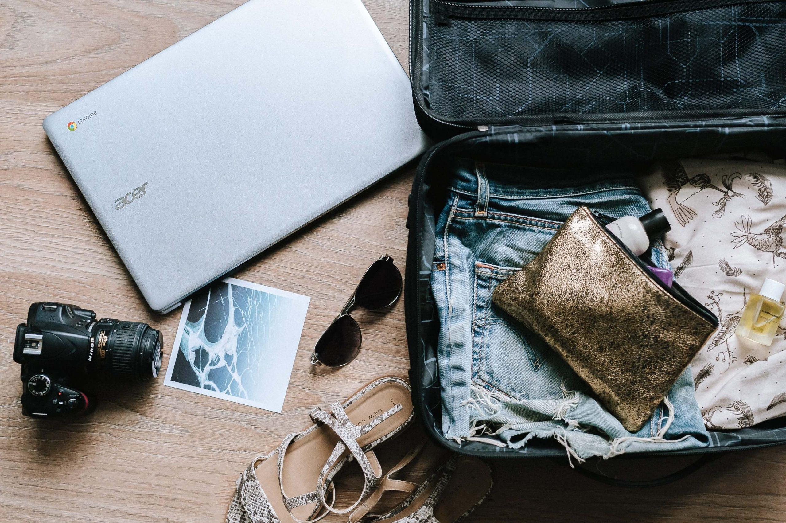 Mala de férias de verão com roupa, acessórios, computador, máquina fotográfica, óculos de sol e estojo de higiene