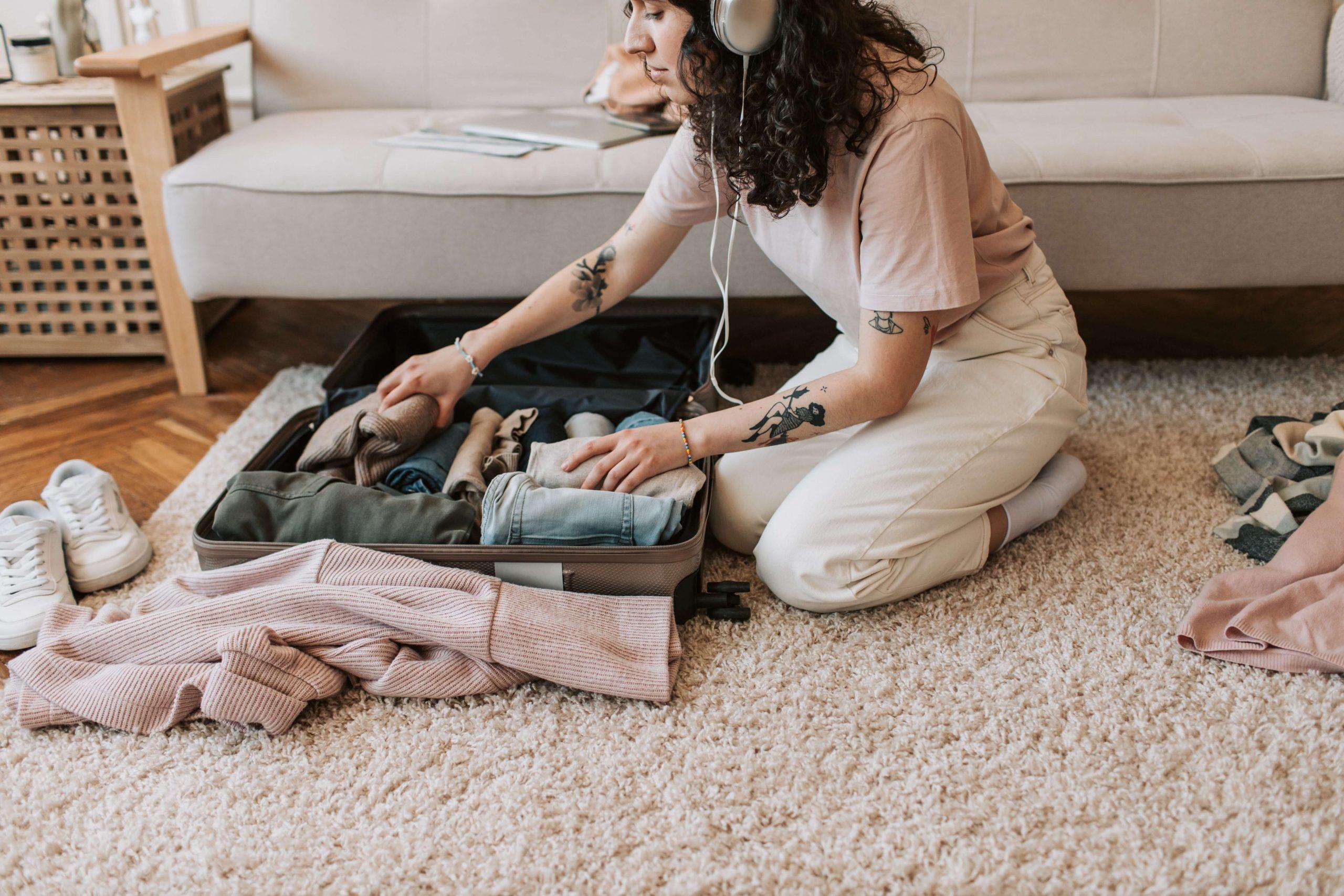 Rapariga a fazer a sua mala de viagem