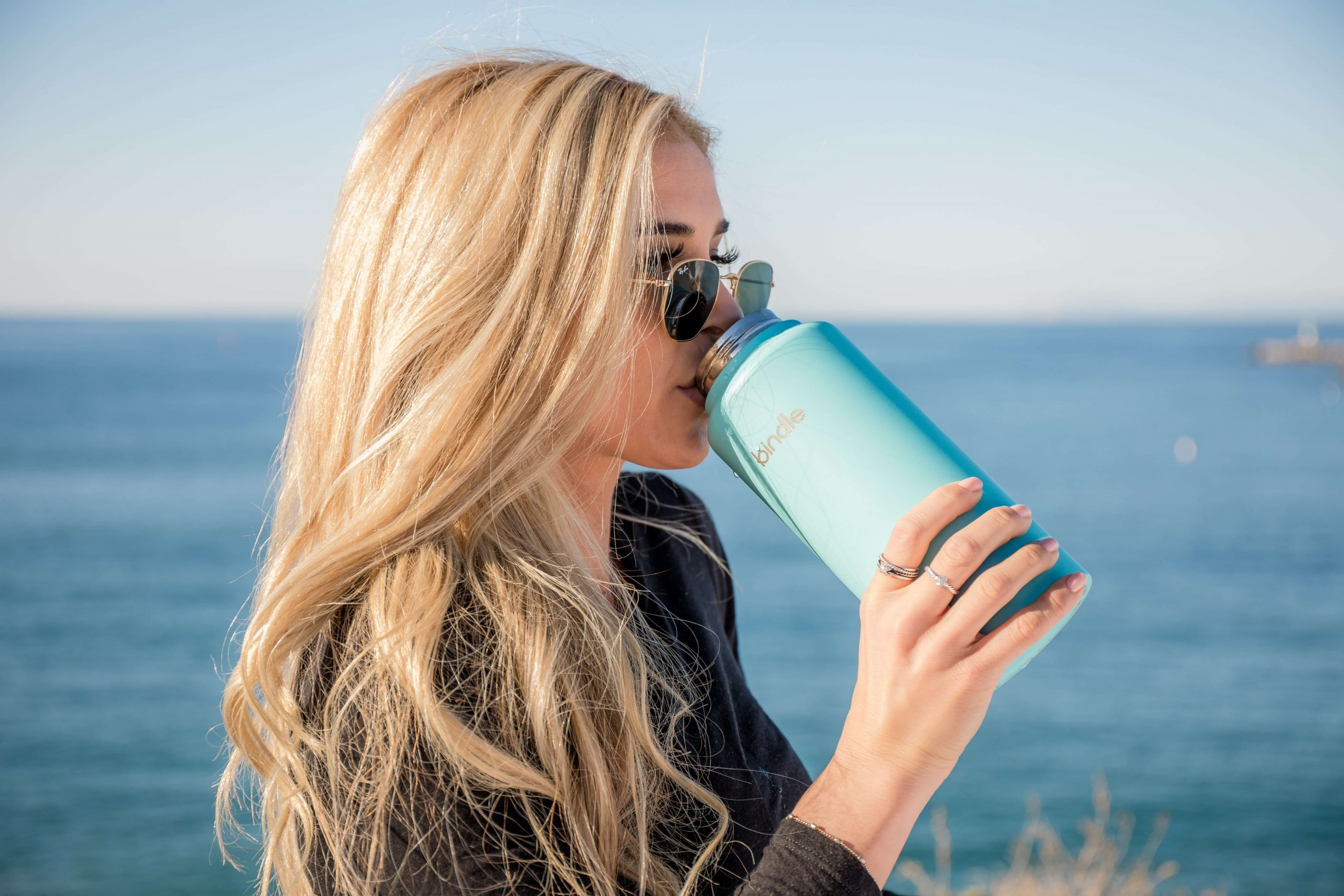 Mulher a beber de uma garrafa de agua reutilizável a beira mar