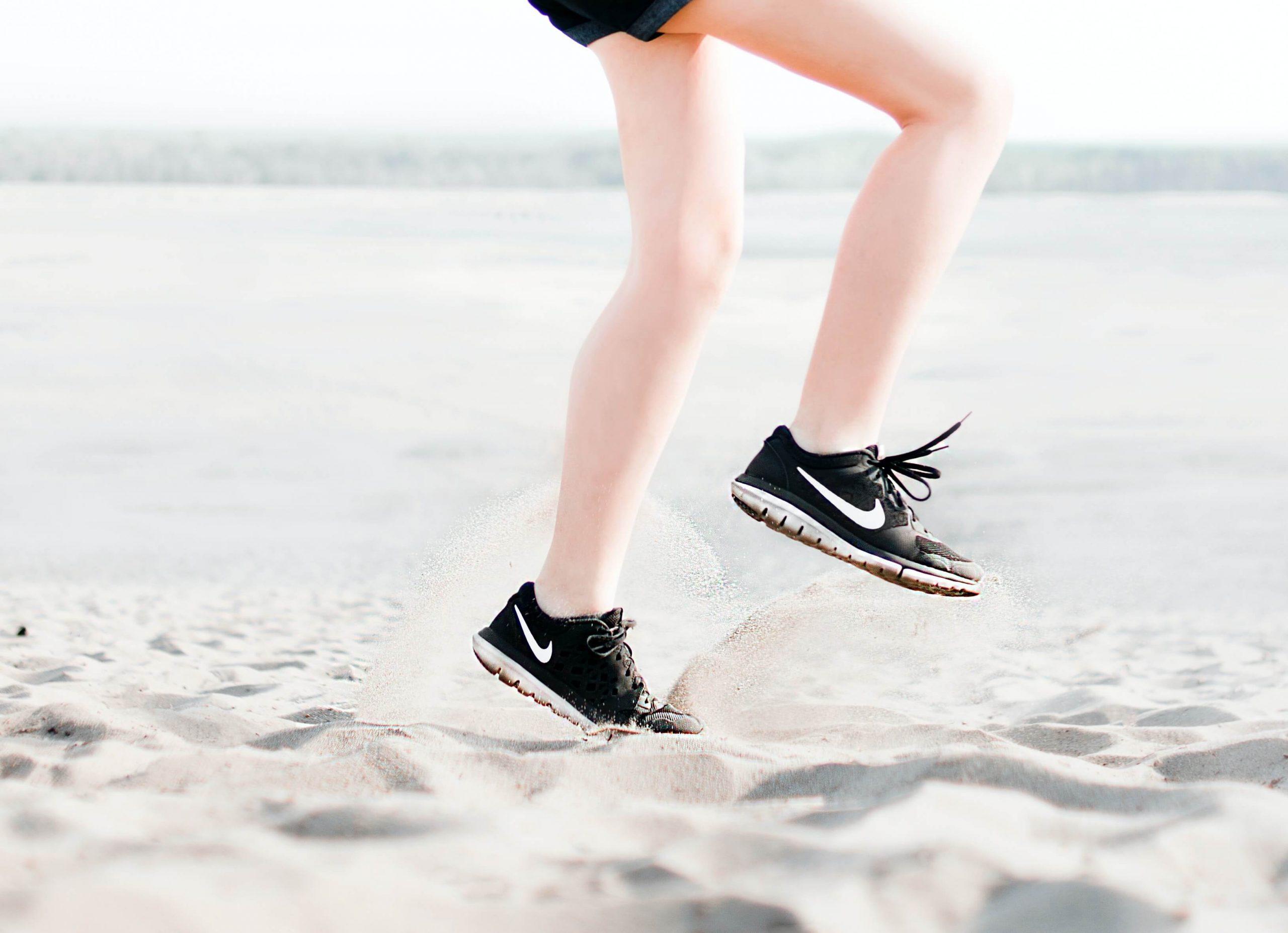 detalhe de pernas de pessoa a correr na areia